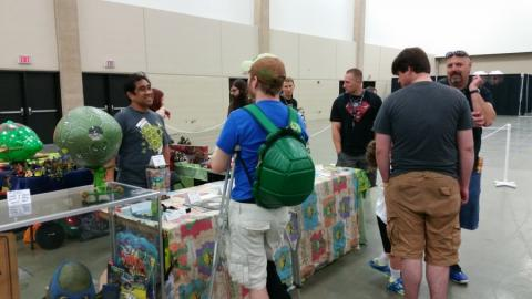 Fugitoid and Hit Girl working the Cowabunga Corner booth while fans ask questions and check out the collection.